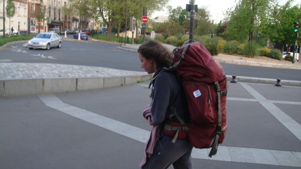 Raquel, autora do blog, caminhando com uma mochila grande de viagem nas costas em seu primeiro mochilão para a Europa em abril de 2009