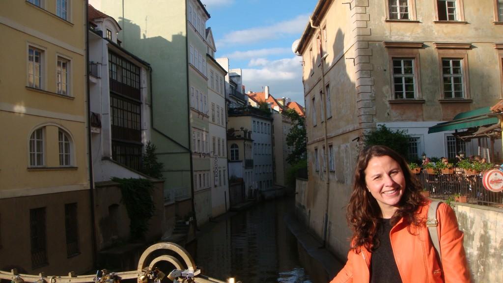 Raquel, a autora do blog, aparece no canto direito da foto sorrindo, atrás dela tem um canal onde passa um pequeno rio por entre os prédios históricos do bairro de Malá Strana em Praga