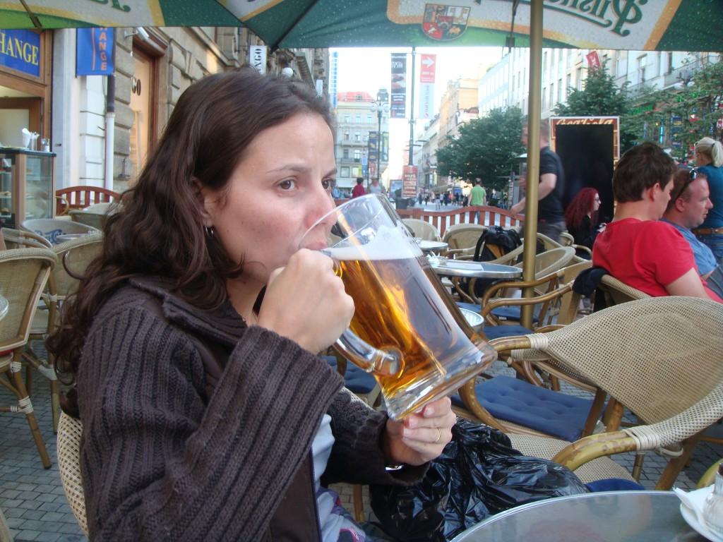 Autora do blog, Raquel, segurando com as duas mãos e tentando beber um caneco de 500 ml de cerveja