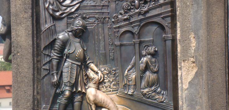 Gravura em alto relevo colocada na base da escultura de São João Nepomuceno na Ponte Carlos em Praga. A imagem retrata um esculdeiro fazendo carinho em um cão.