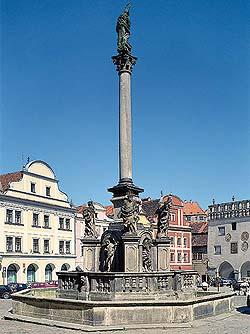 foto atual de uma coluna rodeada por uma fonte na praça principal da cidade medieval de Cesky Krumlov na República Tcheca