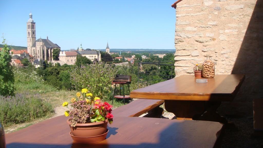 mesas de madeira com vaso de flores naturais em cima, as mesas estão disposta em um jardim na rua com vista para um bonito vale