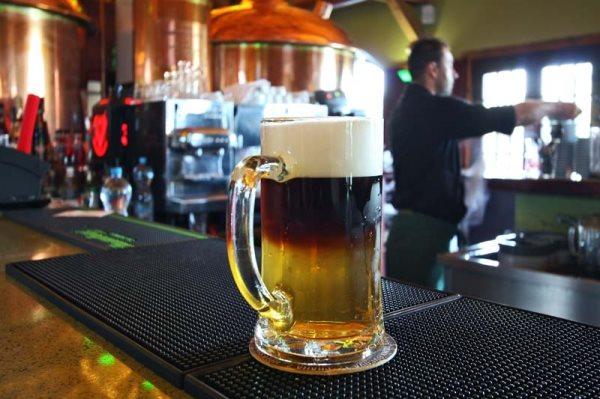 balcão de bar com um caneco de chopp de 500 ml em primeiro plano