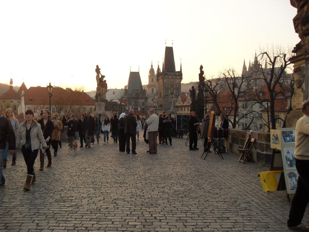 pessoas passeando pela ponte Carlos em um fim de tarde de tempo bom em Praga