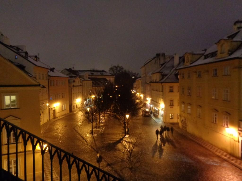 Foto noturna do bairro de Malá Strana em Praga, com iluminação amarelada valorizando a arquitetura dos prédios