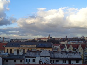 Imagem da cidade de Praga tirada do alto, aparece o telhado das casas. O céu está azul com nuvens espessas
