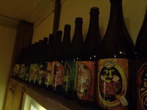 Garrafas de cervejas uma ao lado da outra em uma prateleira