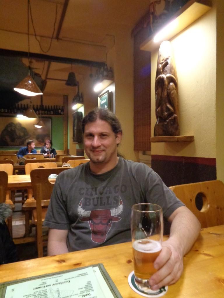 Giovani sentado em uma mesa de bar tomando cerveja