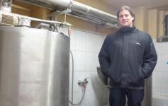 Giovani ao lado de um silo de metal que guarda a cerveja pronta