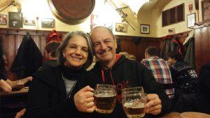 Clientes do Praga Boêmia, Angelina e Ricardo, no beer tour, brindando com um caneco de 500 ml de cerveja pilsen em um pub