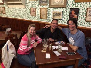 Casal sentado em uma mesa de bar acompanhados do guia do beer tour Jan