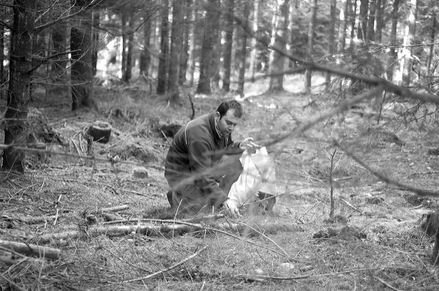 homem abaixado na floresta colhendo cogumelos