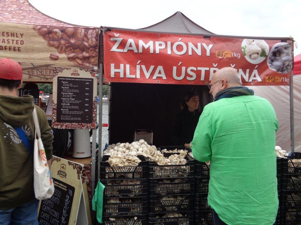 um homem parado em uma barraca de cogumelos em uma feira de rua
