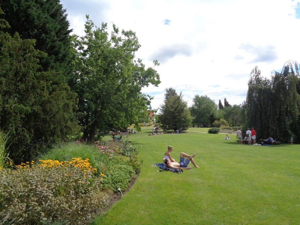 pessoas descansando em uma grama verde bem cuidada de um jardim botânico
