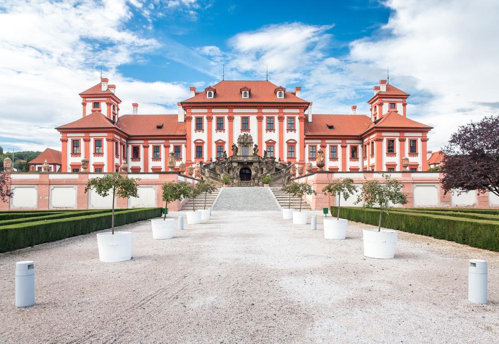 frente de um palácio em estilo barroco pintado em branco e salmão