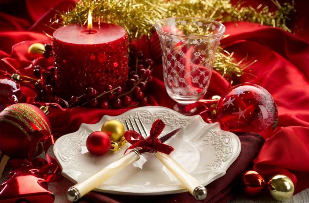 mesa de fim de ano preparada especialmente com uma toalha vermelha, vela acessa vermelha, bolas de Natal e um prato branco com talheres cruzados em cima