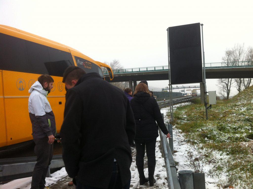 Pessoas fumando na frente do ônibus da empresa Student Agency quebrado na estrada