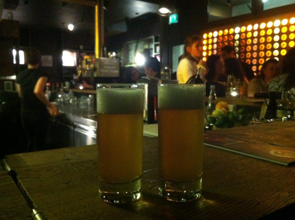 Dois copos de cerveja pequenos no balcão de um bar