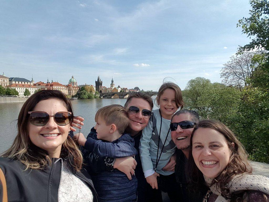 Família com crianças posando para a foto com a Ponte Carlos de Praga ao fundo