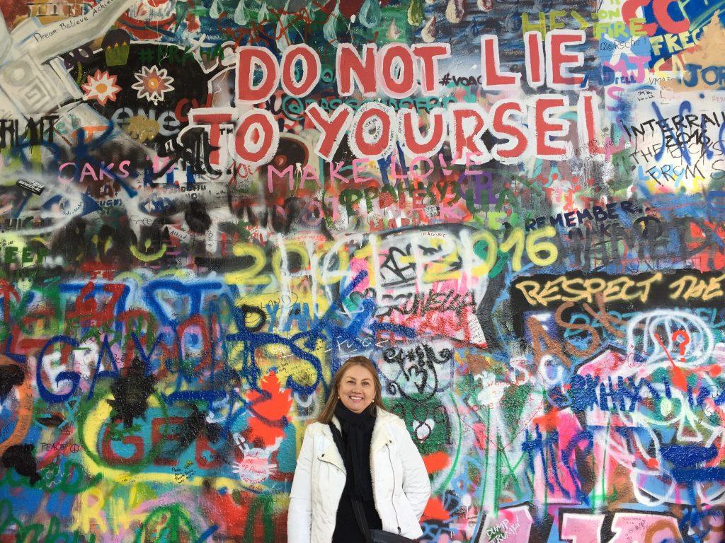 Turista sorrindo e posando para foto em frente ao Muro de John Lennon em Praga, República Tcheca