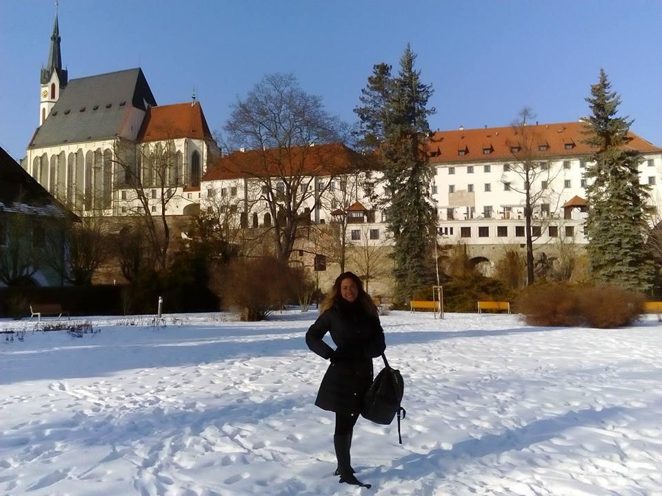 Moema, cliente do tour privativo do blog, em frente a um monumento importante da cidade Cesky Krumlov em um dia de sol com muita neve