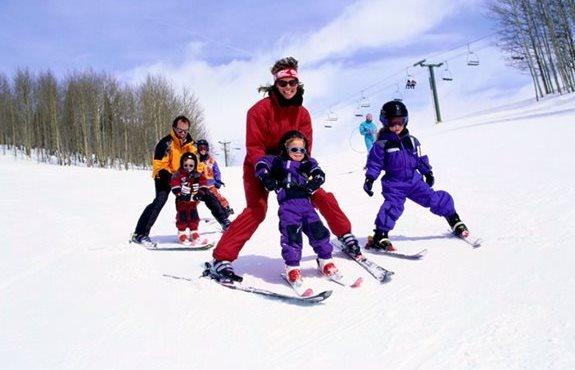 Família com crianças esquiando na estação de esqui de Monínec