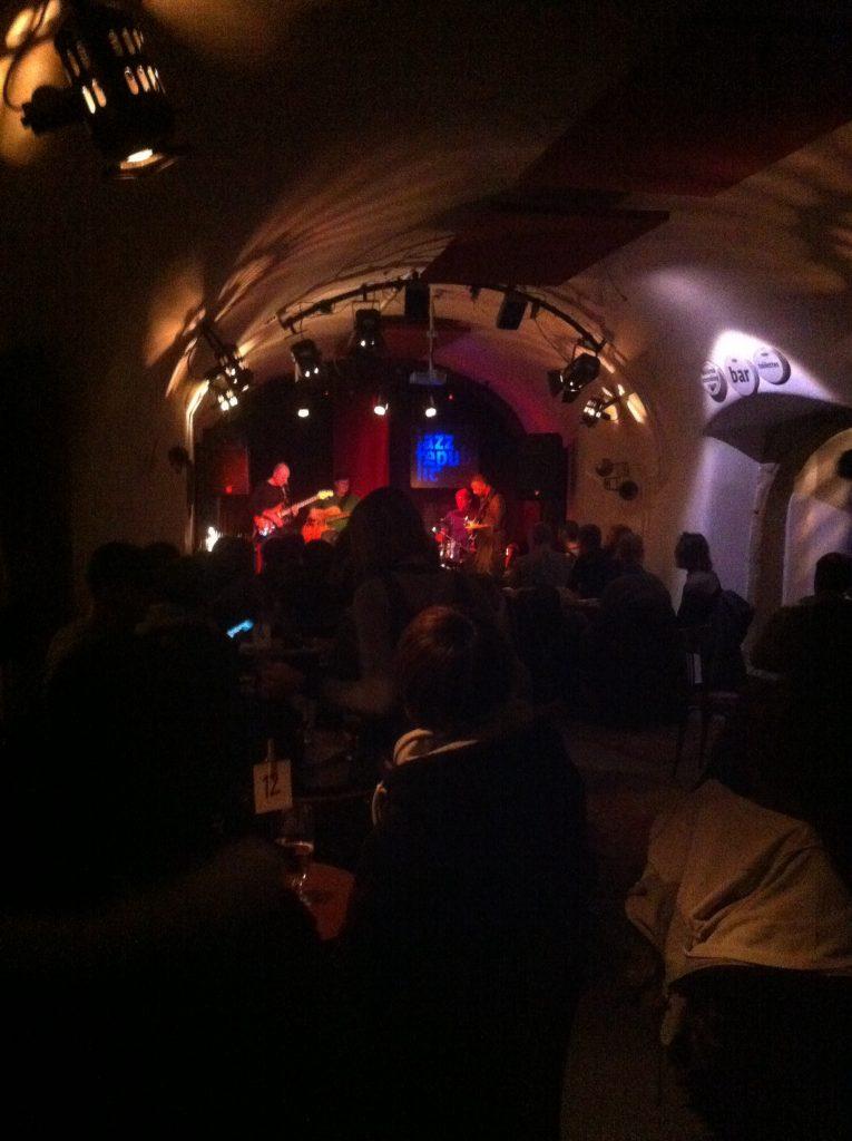Club de jazz em Praga com banda se apresentando no palco e várias pessoas sentadas na mesa na frente da banda
