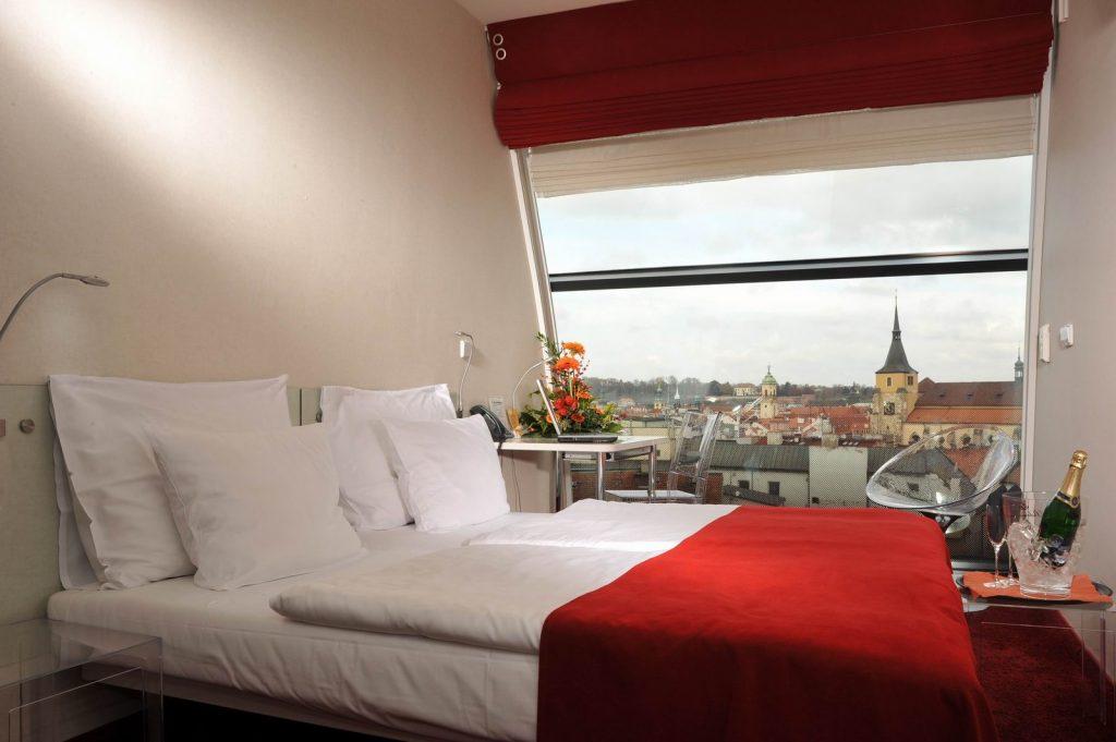 Quarto duplo de hotel decorado de forma moderna com uma janela grande com vista para a Cidade Velha de Praga