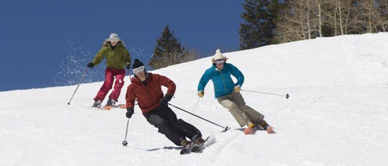 Três esquiadores fazendo manobras enquanto descem uma montanha nevada