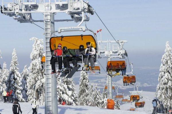 Quatro pessoas em uma cabine/teleférico em uma estação de esqui