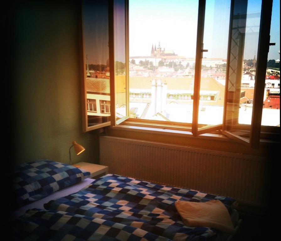 quarto de um hostel em Praga, mostrando a janela aberta com vista para o castelo de Praga