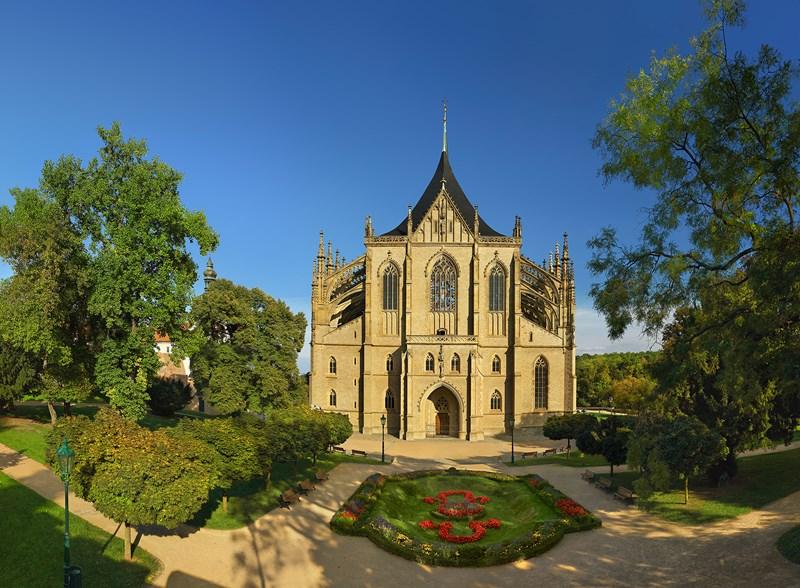 Fundo da Igreja de Santa Barbara em estilo gótico medieval com um jardim bem cuidado à frente e um céu azul de verão ao fundo