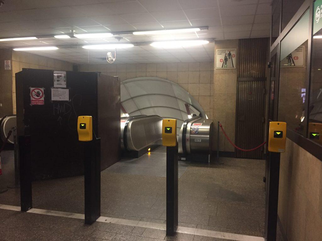 Metrô de Praga, entrada para o acesso ao metrô, com máquinas amarelas para validar os tickets
