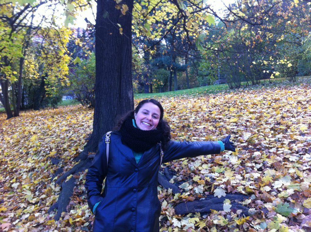 Raquel, autora do blog, mostrando o chão coberto de folhas no outono de Praga