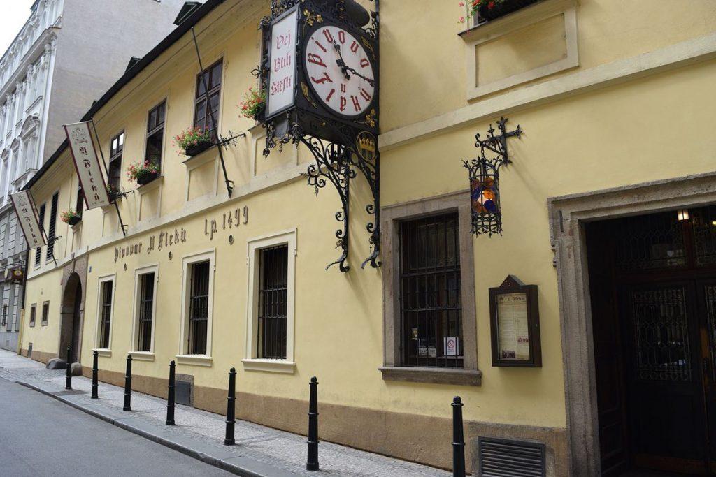"""Fachada de entrada da cervejaria U Fleku com seu particular relógio avisando que é hora de tomar """"pivo"""" (cerveja em tcheco)."""