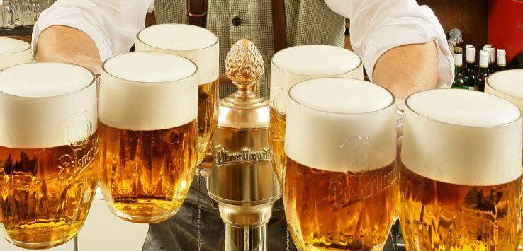 Garçom com várias canecas de 500 ml de pilsner no restaurante histórico U Pinkasů em Praga, República Tcheca