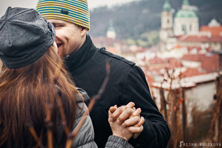 Casal se beijando em close e o bairro de Malá Strana do alto ao fundo desfocado