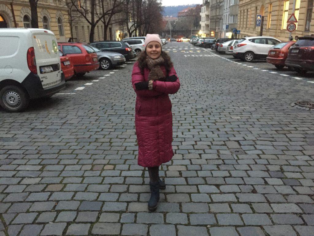 Foto da Raquel, autora do blog, bem no meio de uma rua em Praga, vestida com casaco mais pesado de inverno